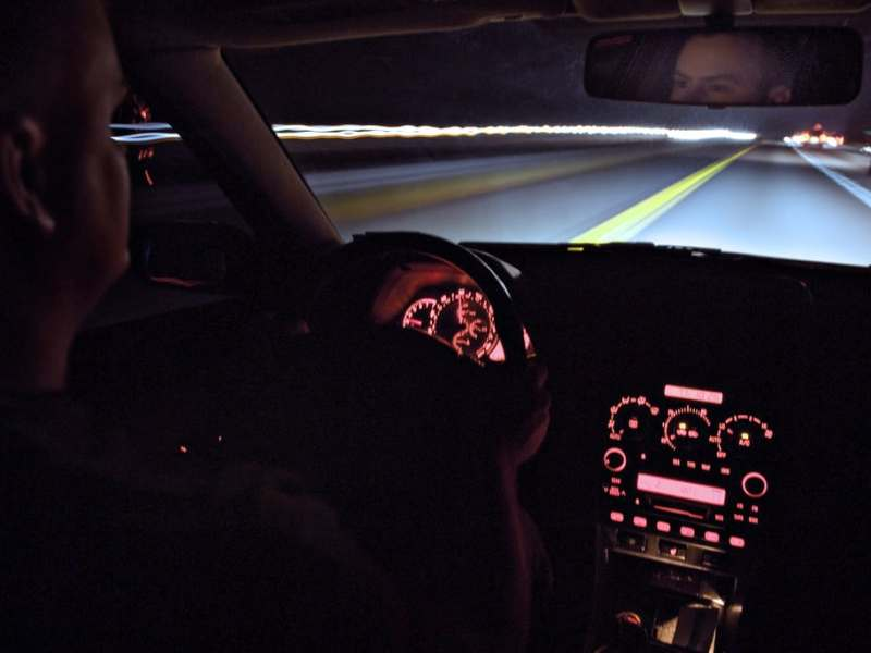 shows the interior of a car at night, looking out at a poorly lit road