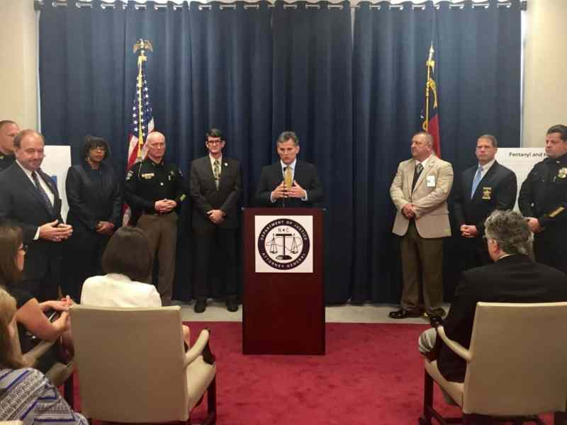 Stein stands at podium, surrounded by a bunch of law enforcement officials