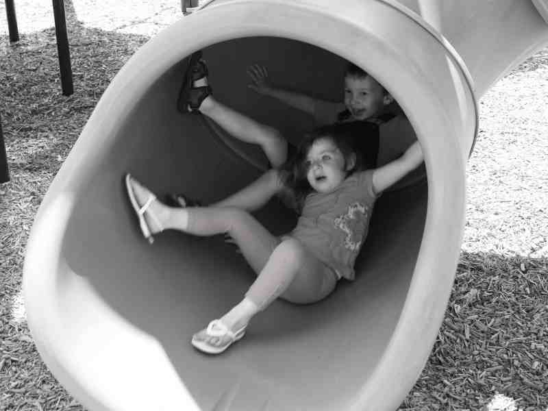 shows children looking frightened as they tumble down a slide