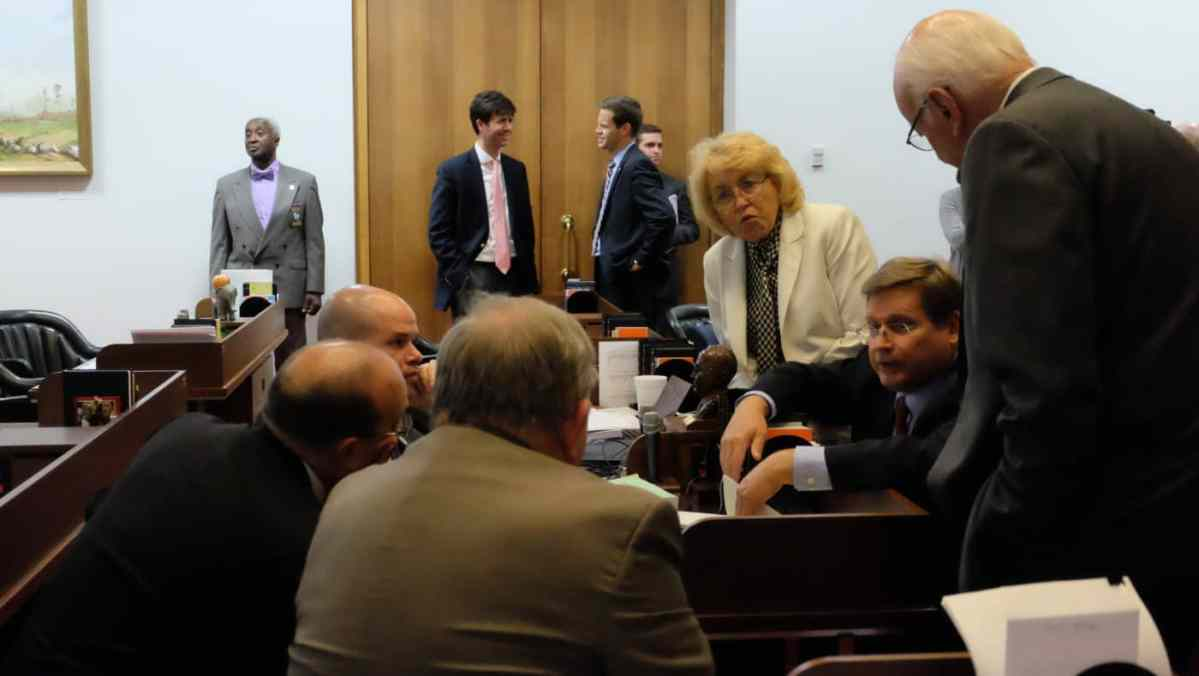 shows a group of people huddled around a desk