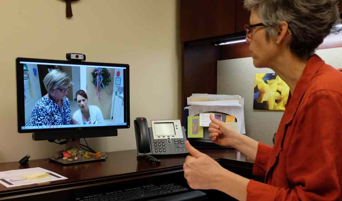 ECU dietician Jill Jennings gives the thumbs up to Duplin schools nurse Ellen Cottle as she completes a demonstration of her telehealth/ telemedicine equipment.