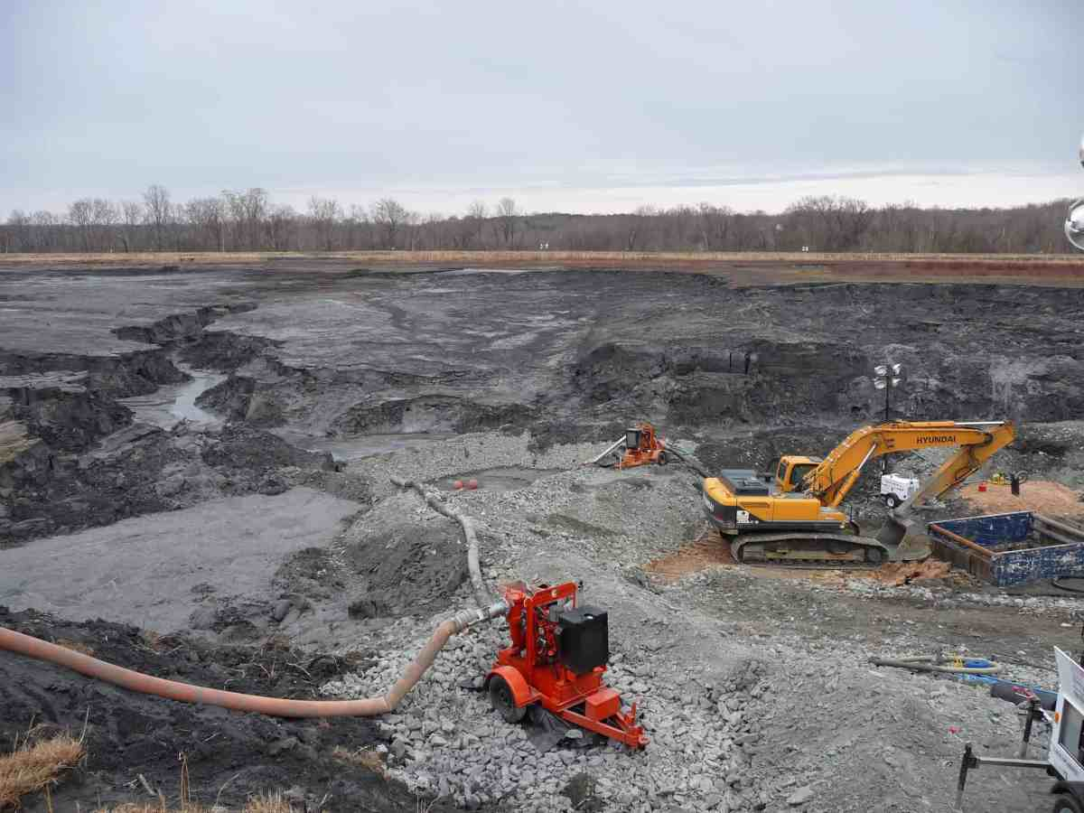 shows vast grey impoundment with earth movers on top