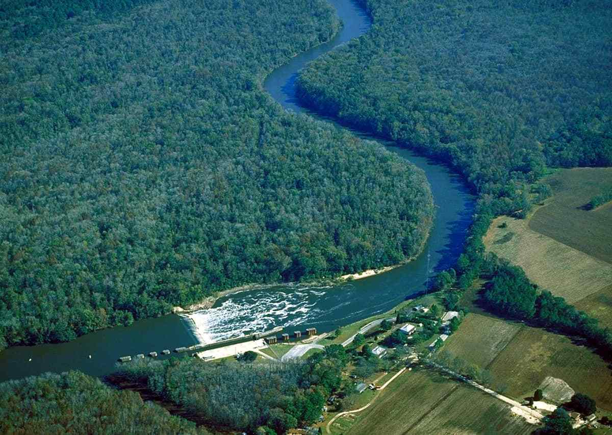 shows low level satellite photo of a dam feeding into a river, surrounded by trees
