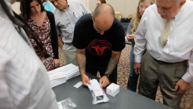 man with heavily tattooed arms puts a box into a plastic bag to build a naloxone kit, which helps treat opioid overdoses, as others stand around hime, looking on.