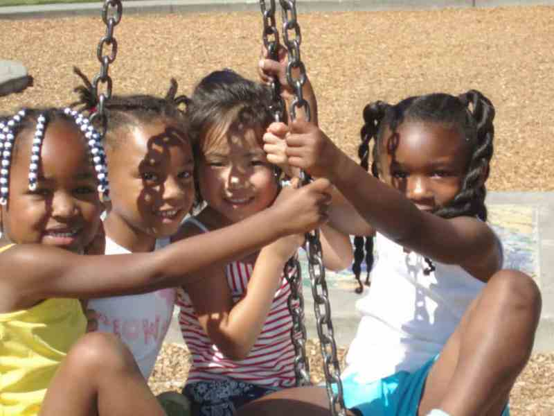 four girls on a swing suspended by chains, they all smile at the camera