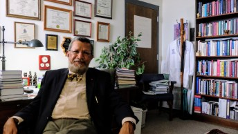 shows Saeed in his office, awards and diplomas on his wall behind him