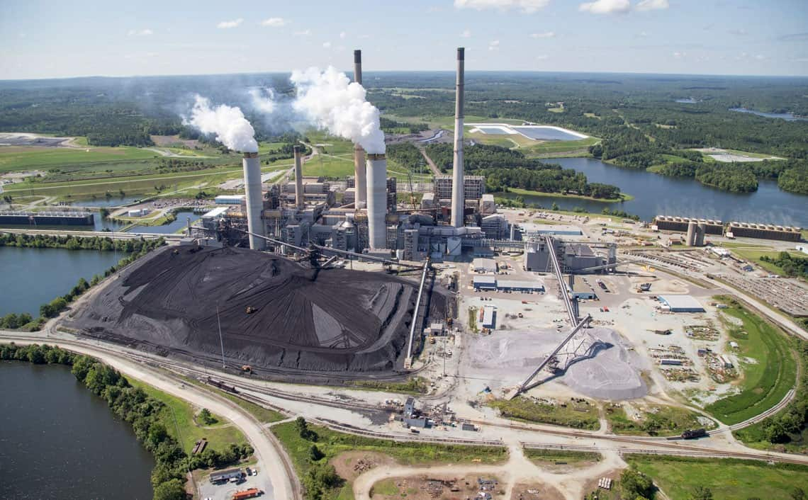 shows a coal plant with steam puffing from one of the smokestacks, a concern in the fight against climate change, air pollution