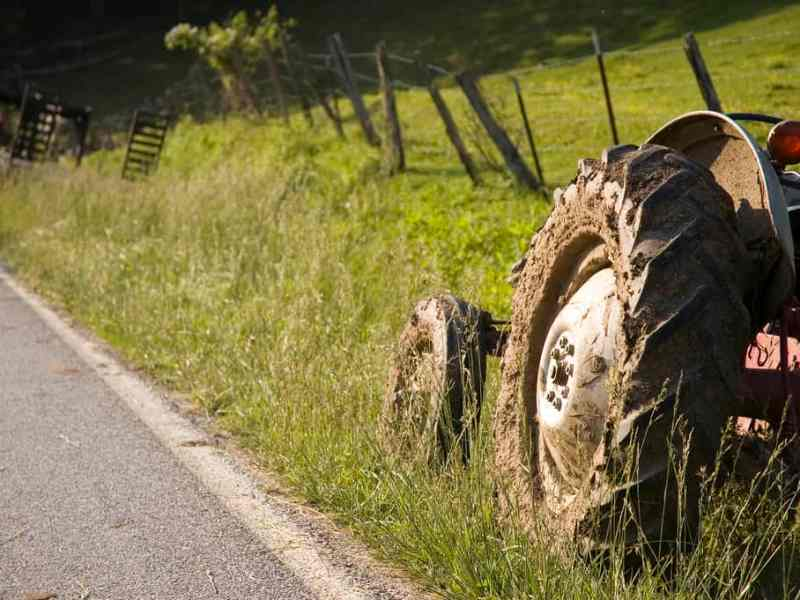 shows tractor wheel in the grass, just off the tarmac on the side of a road, purportedly near Waynesville, NC