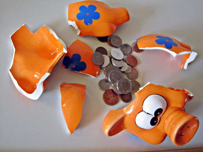 shows a broken piggy bank with coins among the pieces
