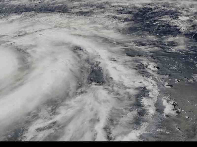 Shows satellite view of large hurricane with well-defined eye