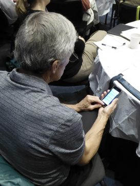 Over the shoulder, the photo shows a grey haired man marking off a question on his cell phone