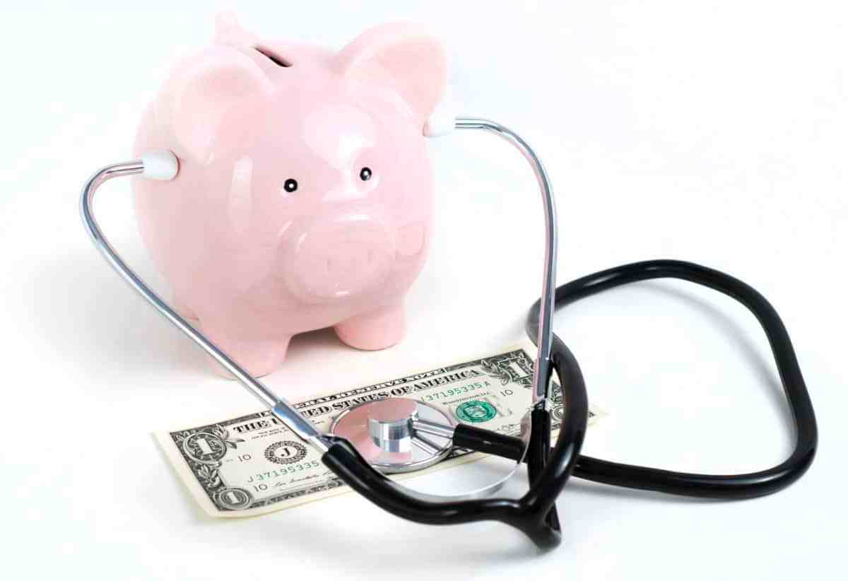 shows a pink piggy bank wearing stethoscope and the listening end of the stethoscope is on a dollar bill, spending, money