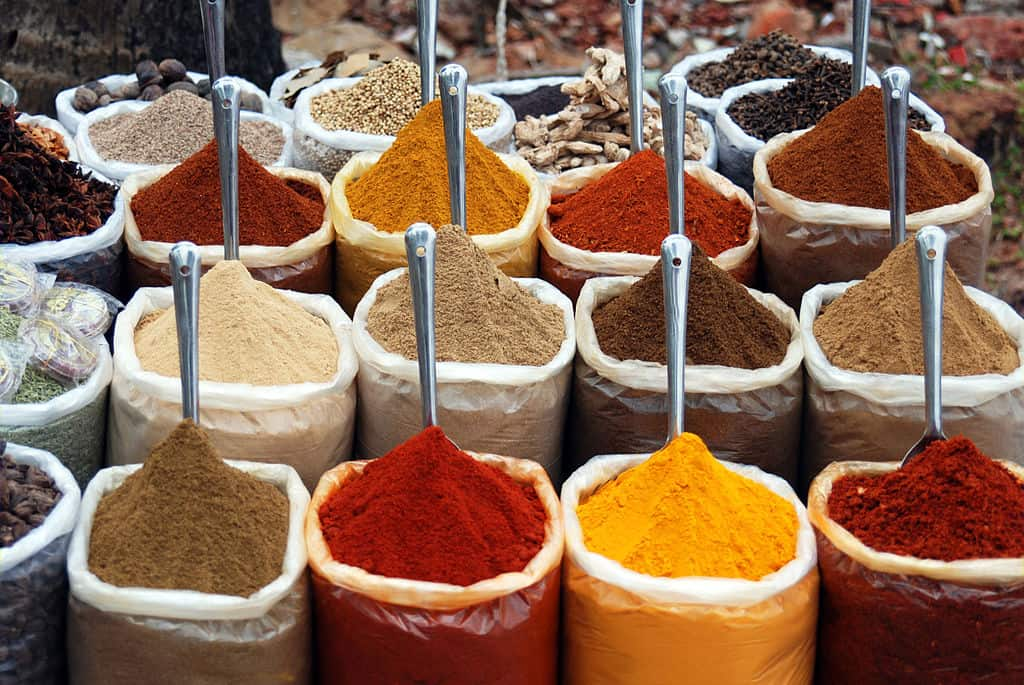 shows colorful ground spices on display, piled up in bags