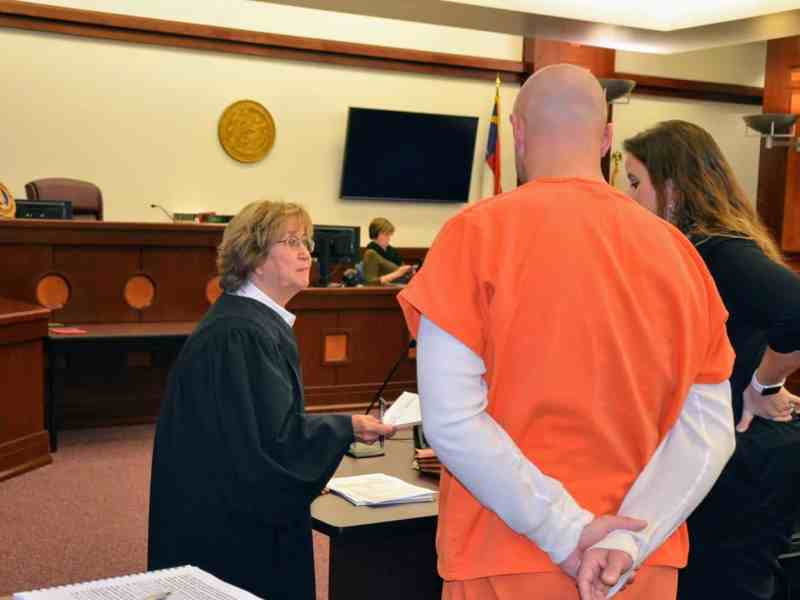 shows an older woman in judge's robes talking to a man with his back to the camera. He's wearing an orange prison jumpsuit.