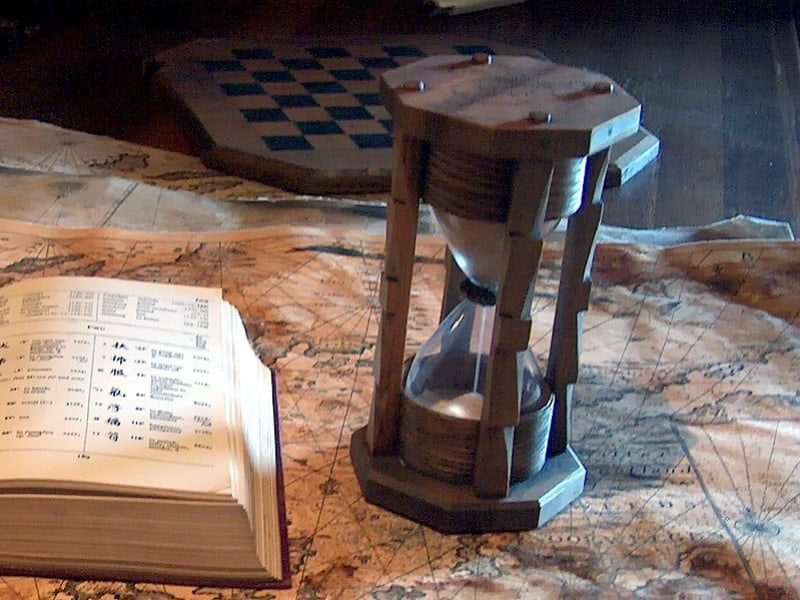shows an old fashioned hourglass, next to a large book. Good image for new years