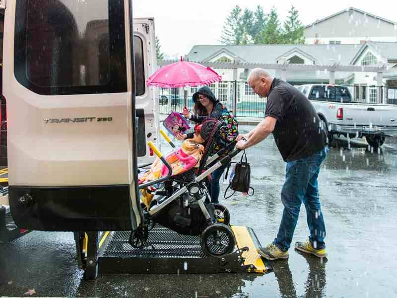 Shows a man in the rain loading a little girl in a stroller into the back of a disabled accessible transportation van.