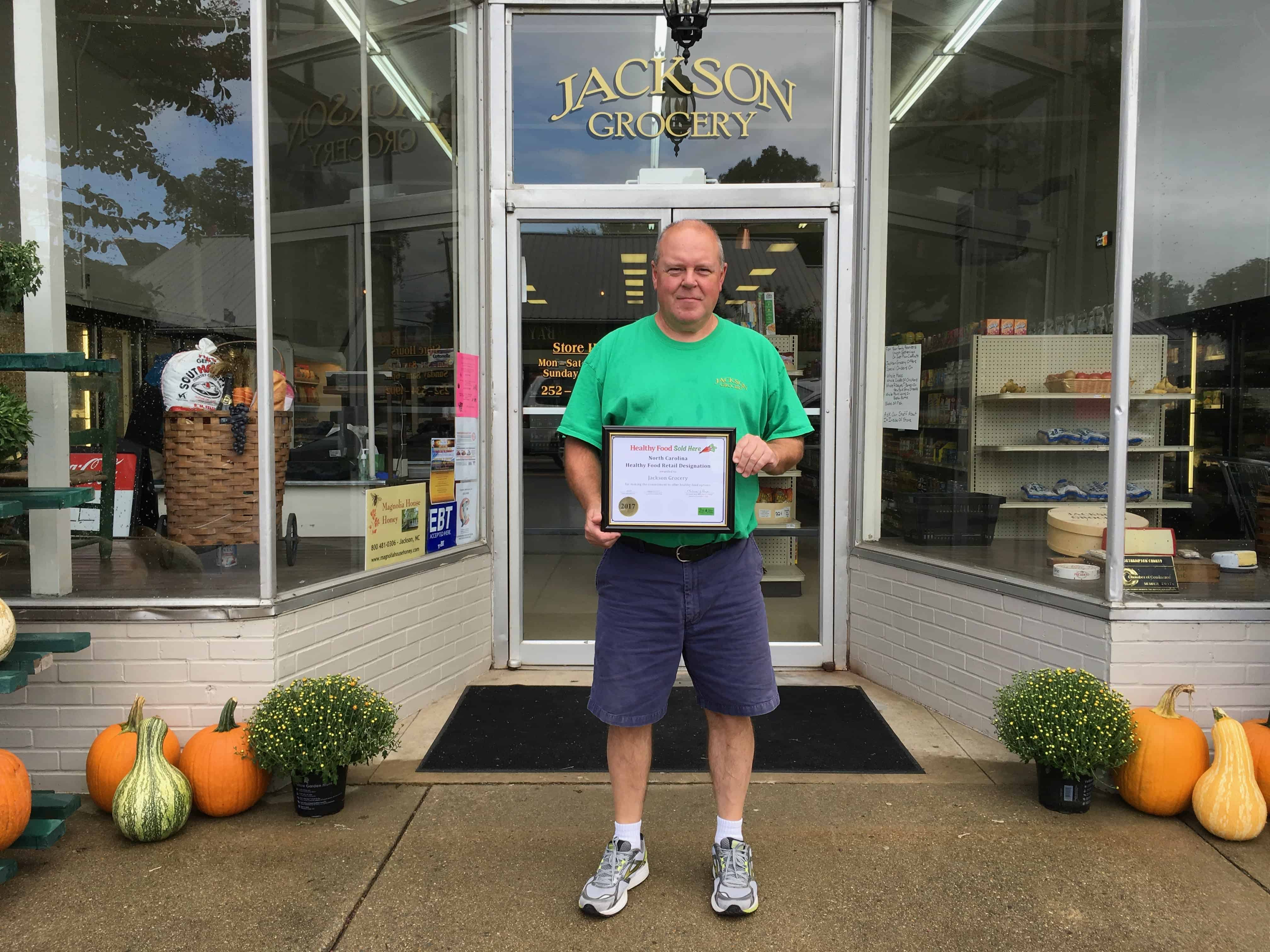 """a man stands infront of a store labeled """"Jackson Grocery"""" and he's proudly holding a certificate"""