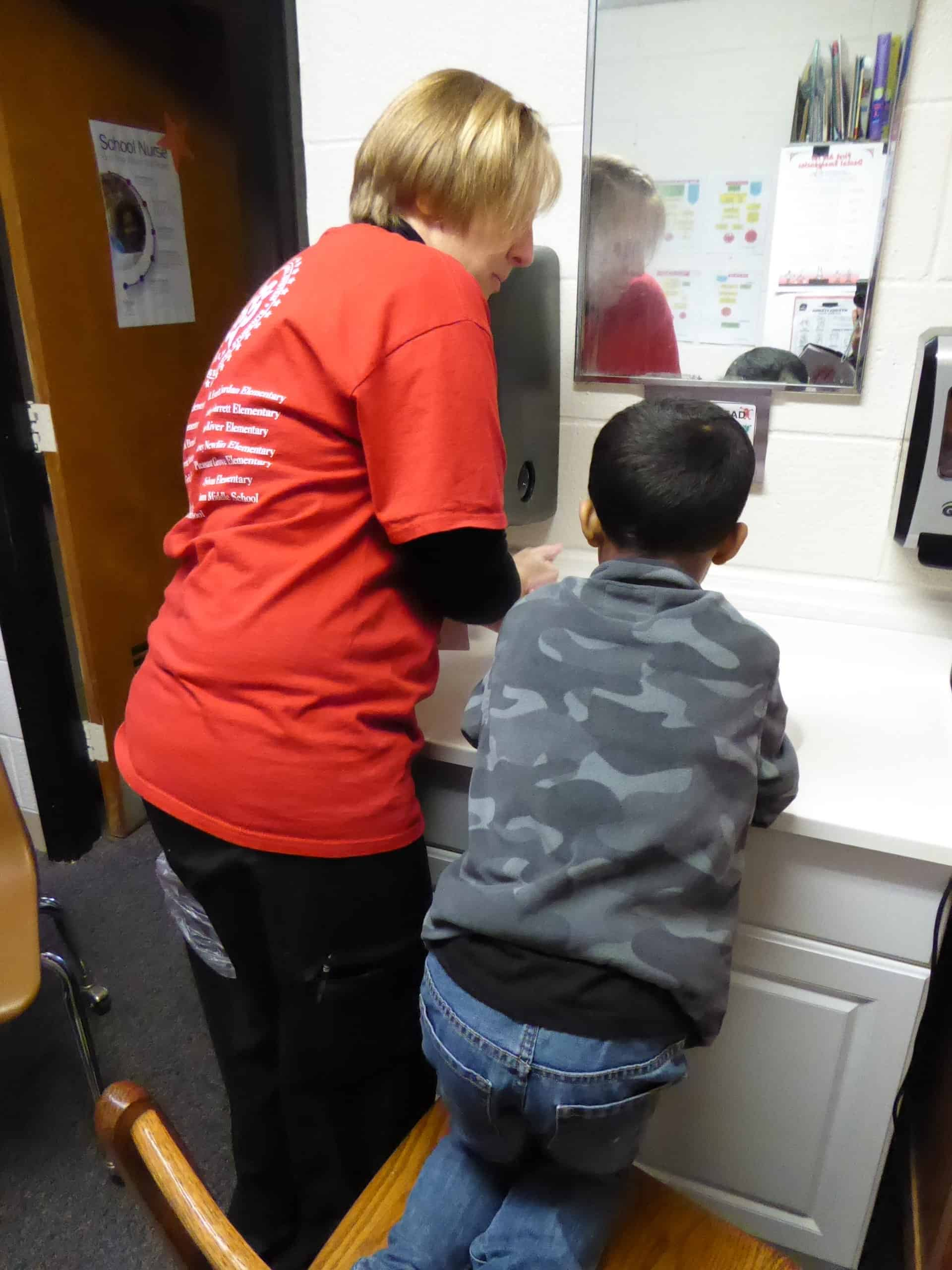 The school nurse stands at the sink with a little boy, they're washing their hands together.