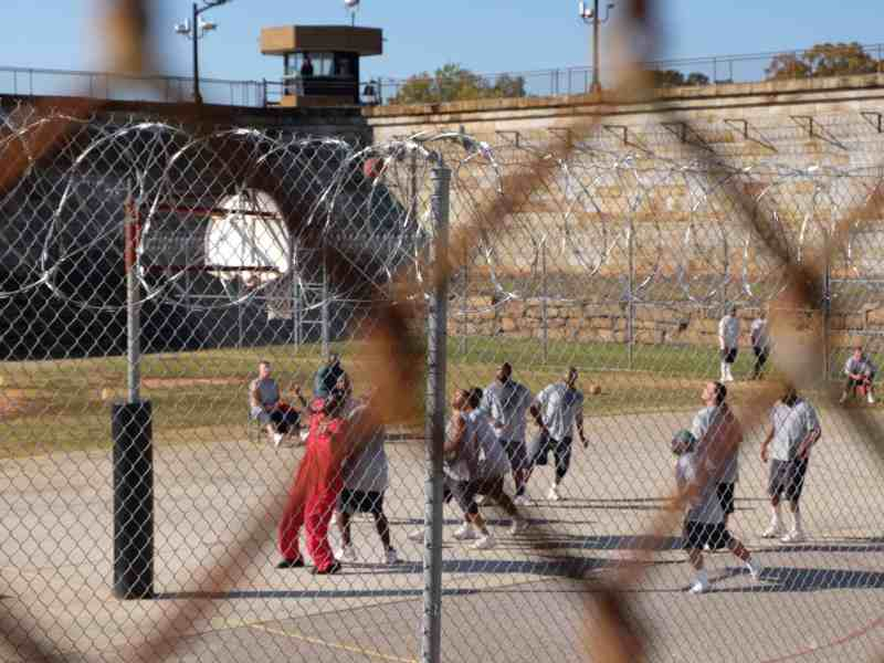 beyond a fence two fences, one topped with razor wire, about a dozen men play on a bleak basketball court. Many people with mental illness end up in the prison system