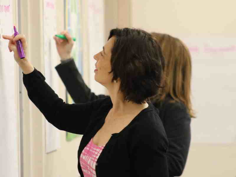 women draw on a whiteboard