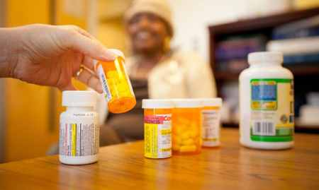 shows a woman's hand holding pill bottle, with SHIIP client in the background