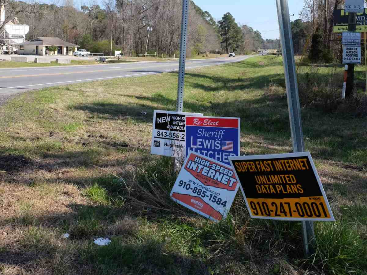 shows signs advertising rural broadband at a lonely rural crossroads. Broadband is necessary for better telehealth penetration in NC's rural burgs.