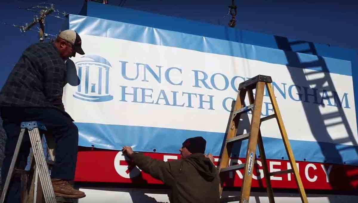 shows two men on ladders placing a blue and white UNC Rockingham sign over a marquee sign.