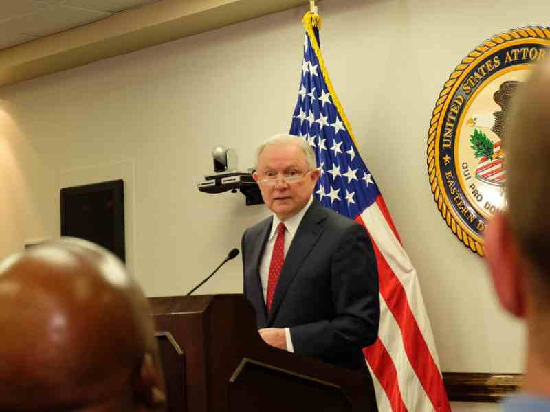 woman stands at a podium speaking behind a microphone, he is looking directly at the camera in this photo