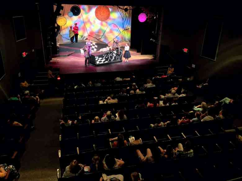 shows a half empty theater with the lights up and actors on the stage