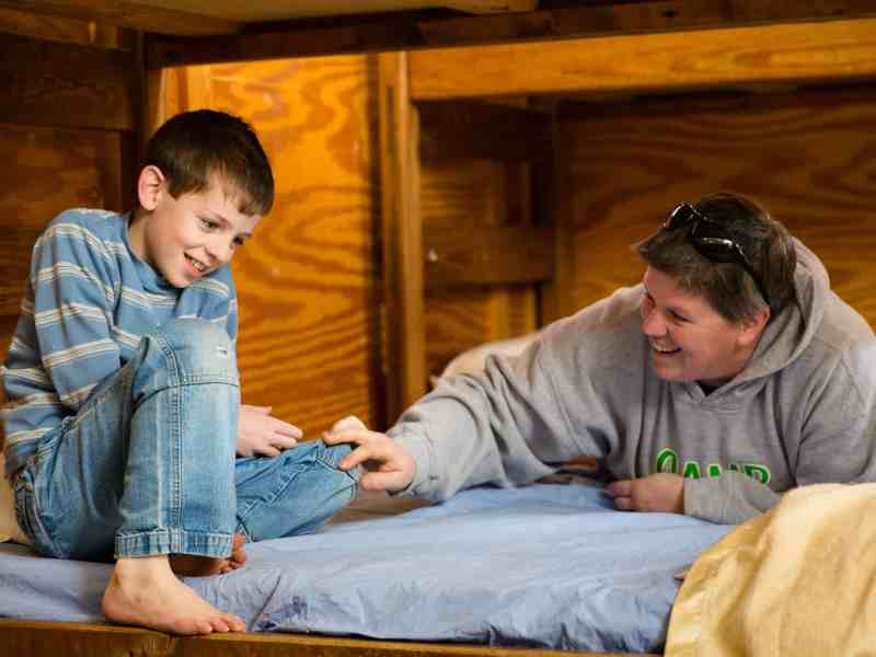 a boy smiles at his ABA therapy counselor