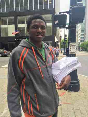 A young African American man stands with a thick sheaf of papers in hte crook of his arm. He's smiling at the camera.