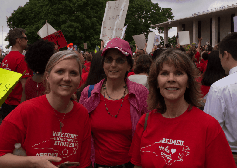 three women dressed in red stand with a large crowd carrying signs behind them, school nurse