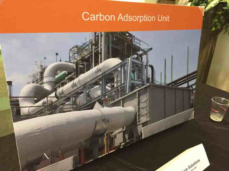 """shows a large format photograph labeled """"Carbon Adsorption Unit"""" sitting on a table"""