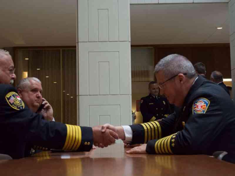 men in dress firefighters uniforms shake hands across a wooden table