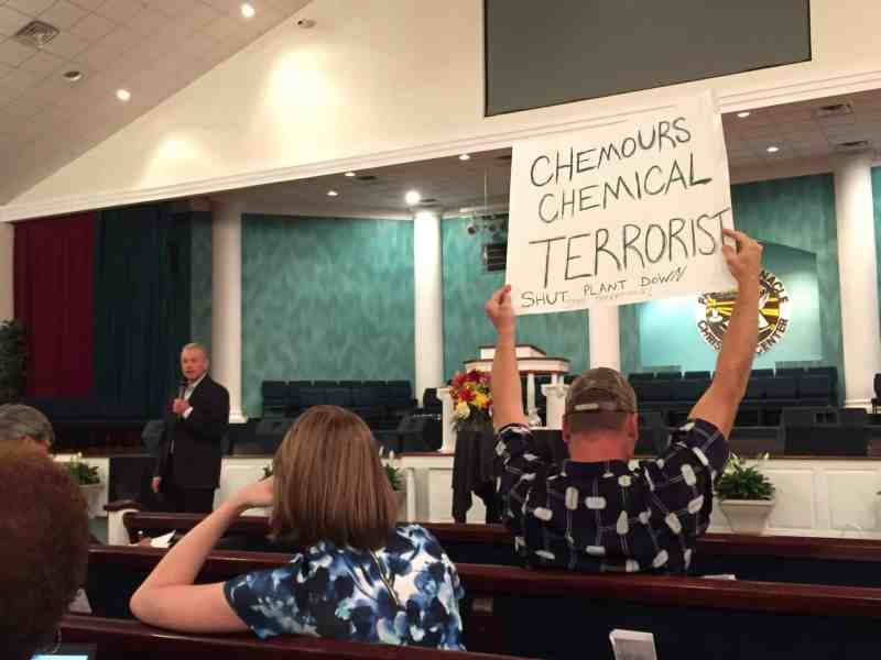 """man holds up a sign reading: """"CHemours Chemical Terrorists - shut the plant down"""""""