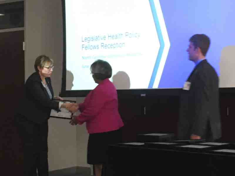 """a woman receives a certificate and a handshake from another woman. theyr'e standing in front of a projection that reads: Insitute of Medicine """"Legislative Health Policy Fellows Reception"""""""