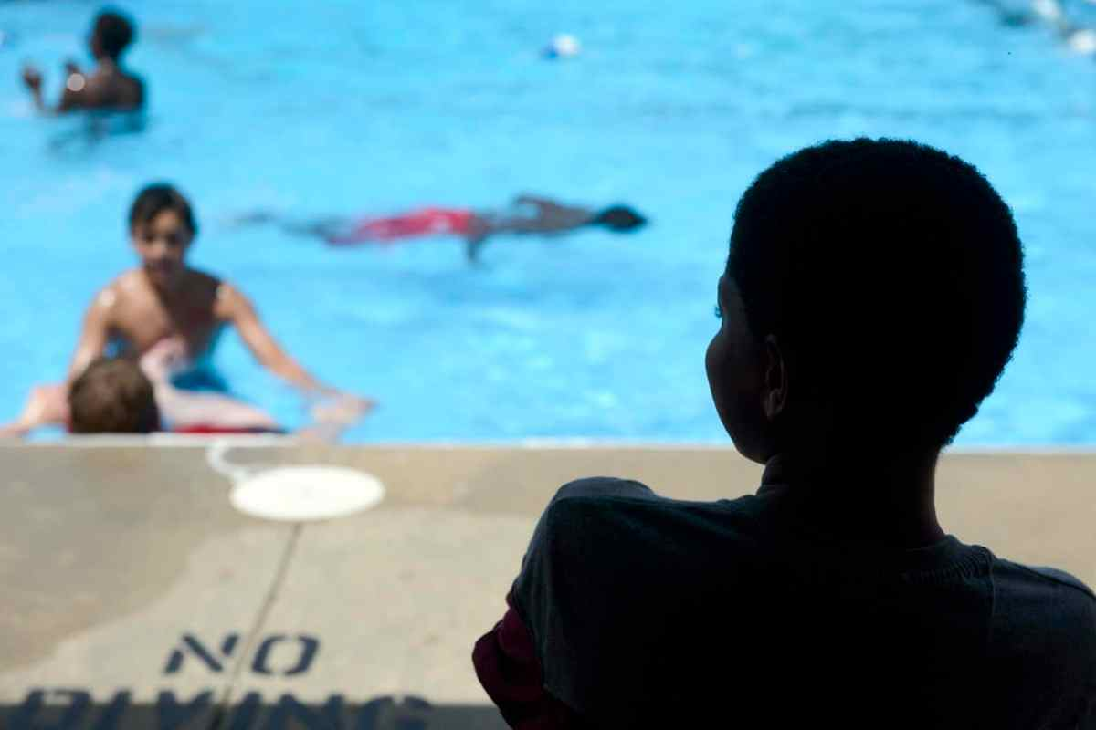 shows the silhouette of a boy, he's looking at a pool where others are playing.