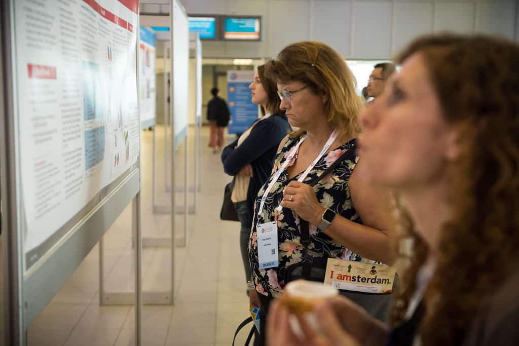 shows people looking at a conference presentation poster