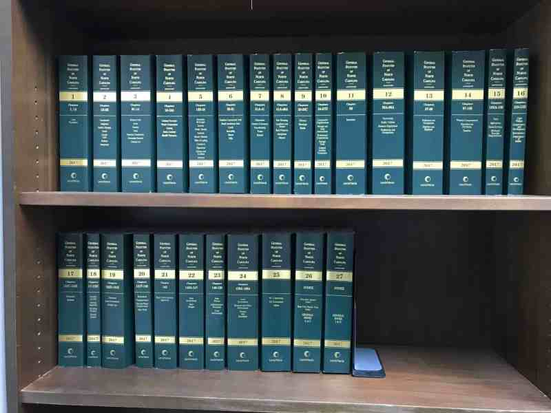 shows two bookshelves filled with 27 volumes of NC General Statutes