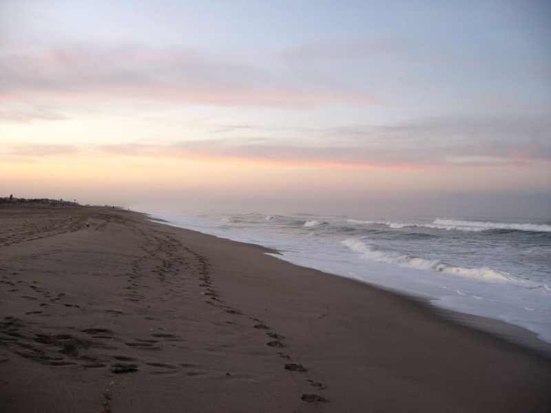 shows a seemingly calm beach at sunrise, but there may be rip currents present