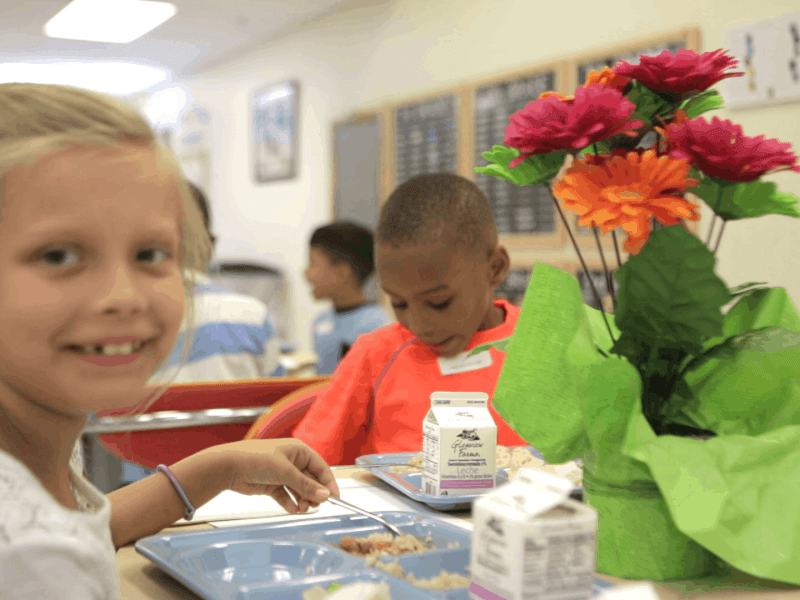 shows a smiling little girl at a table with flowers, a little boy is in the background, just out of focus. they're both at a summer school lunches program. School lunch programs were suspended because of COVID-19, but school districts across North Carolina came up with alternatives.