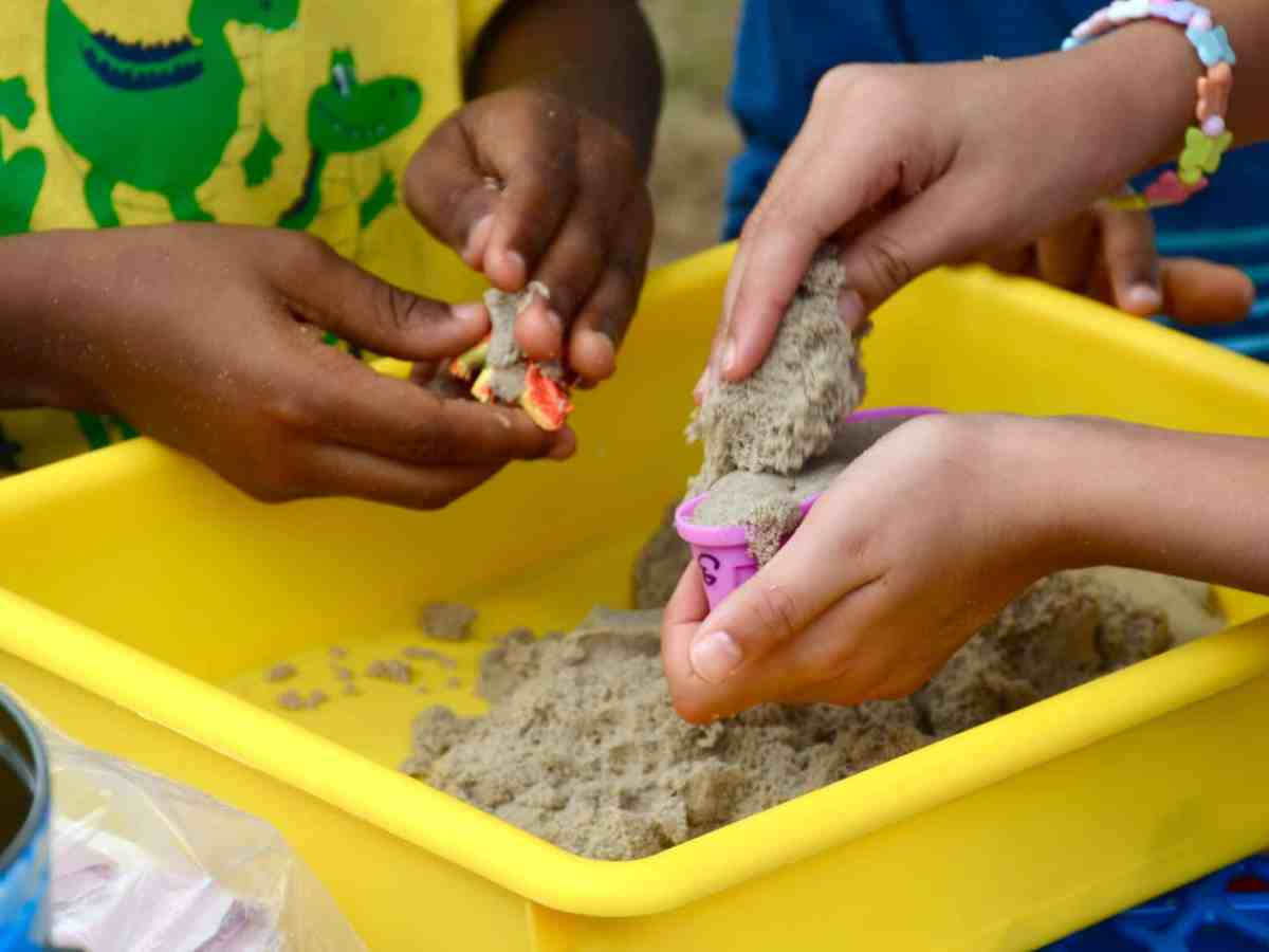 The hands of children attending a summer nutrition program, they're playing with sand.