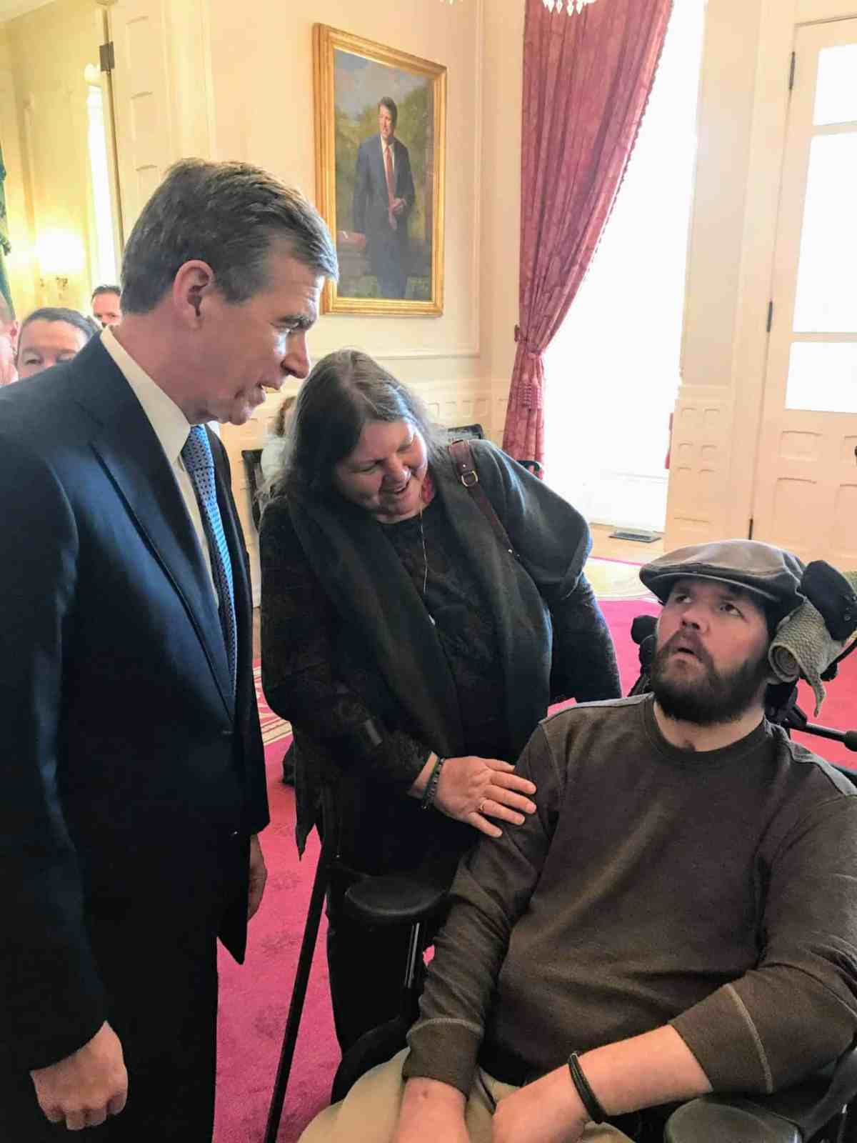 The governor standing on the left greets a man in a wheel chair and his mother, who stands between them.
