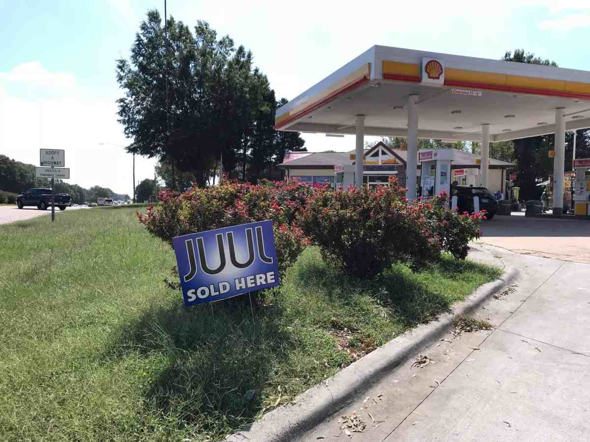 shows the entrance into a refueling station, there's a sign for Juul stuck in the grass next to the driveway