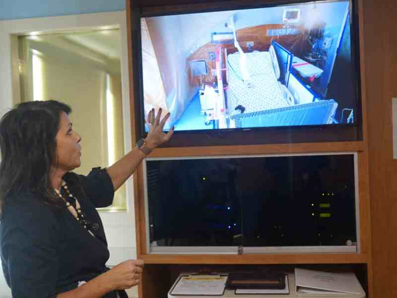 A woman gestures at a video screen which shows the patient bed in the next room over.