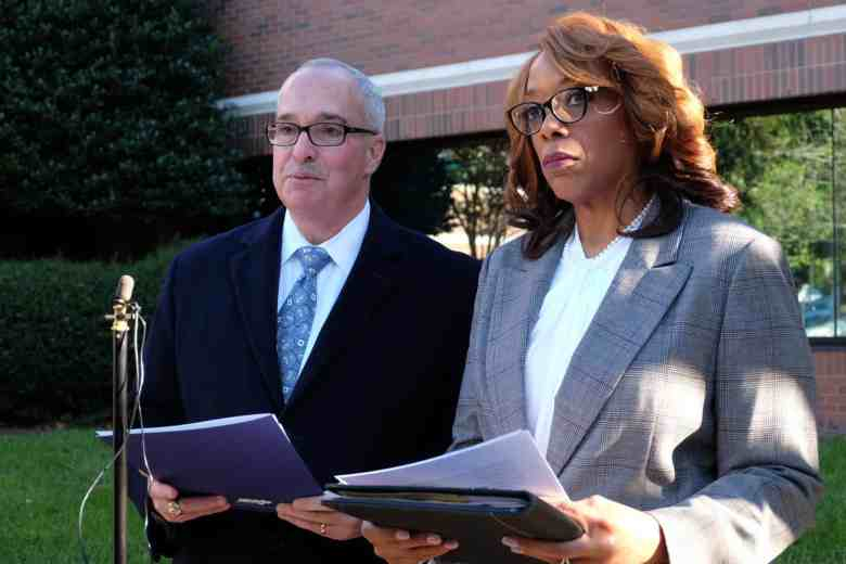 a white man in a suit and tie and an African American woman in a suit stand in front of a microphone in a location that's obviously outside, with a building in the background. They're each holding a sheaf of papers and both looking grim.