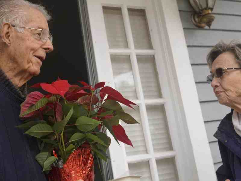 An elderly man in his house's doorway holding a poinsettia, chatting with an elderly woman in a coat outside.