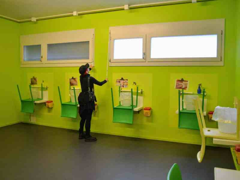 Woman opens up windows in a bright green injection room