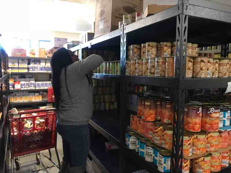 a woman reaches into a shelf stacked with canned goods