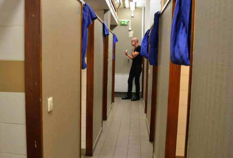 Very tall man at the end of a row of beds